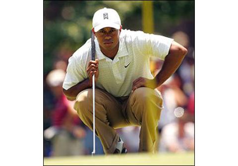 Tiger Woods kneeling for golf shot