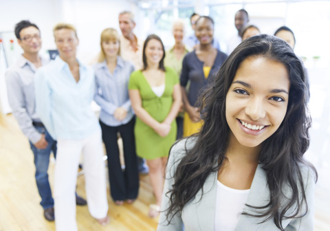 woman in closeup with business professionals in background