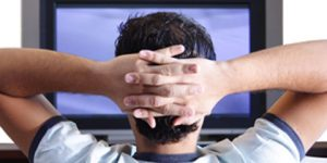 Man watching TV with hands crossed behind head