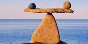 stones on beach balanced on large rock