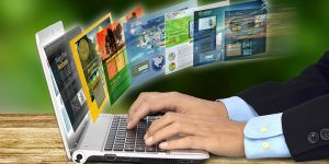 Man on laptop with websites coming out of the screen