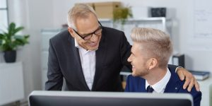 manager smiling with hand on shoulder of employee at their desk