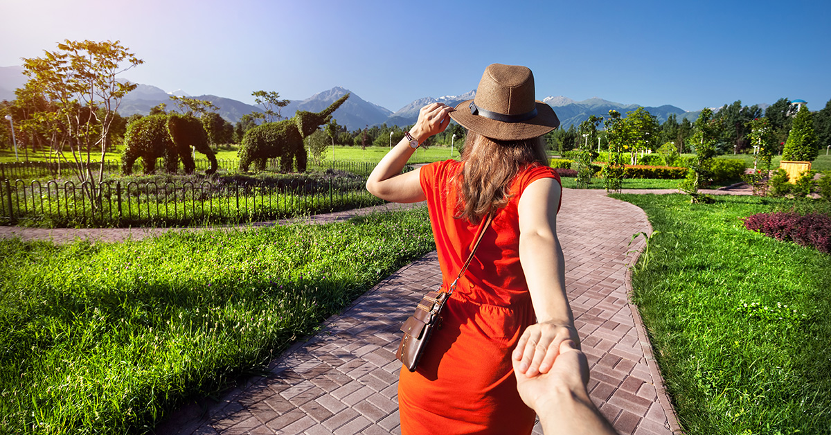 person holding woman's hand in mountain scenery