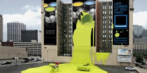 Coops paints building ad with paint down building onto parking lot and car